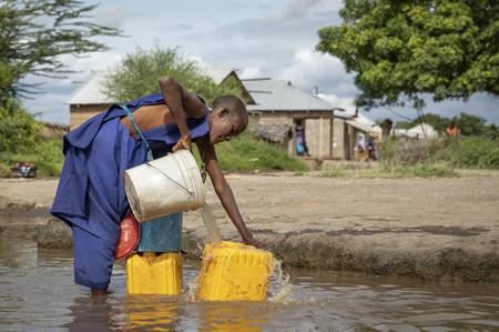 Same, Tanzania, 8th June, 2019:  Maasai woman  at a muddy stream to  collect drinking water