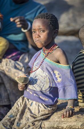 lake Eyasi, Tanzania, 11th September 2019: hadzabe girl eating baobab fruit