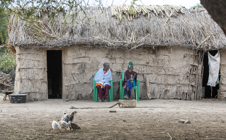 Same, Tanzania, 5th June, 2019:   Maasai couple resting in front of their home Editorial