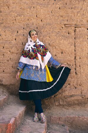 young beautiful Iranian lady in traditional clothing in a traditional village of Abyaneh
