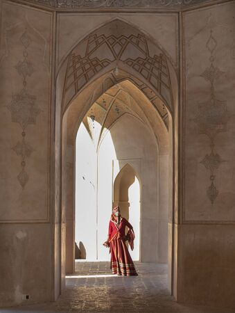 young beautiful iranian lady dressed in red traditional dress in a mosque in Kashan