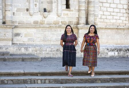 two mayan ladies in their traditional clothing, chatting outdoors