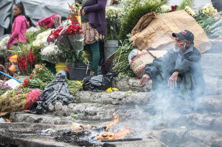 chichicastenango, Guatemala, 27th February 2020: man warming himself by a fire at a market