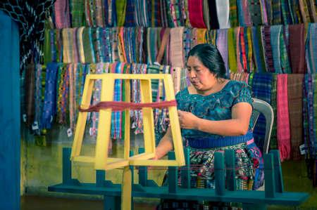 Lake Atitlan, Guatemala, 26th february 2020: mayan woman weaving colorful, traditional fabrics Editöryel