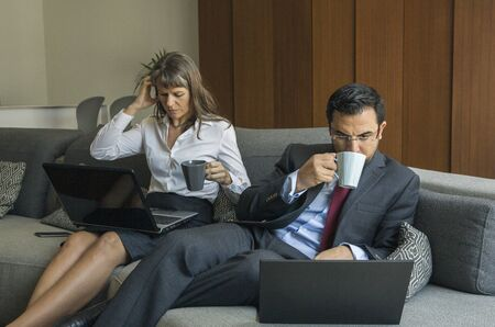 middle aged couple home from work, still in formalware, having a coffee in their city apartment