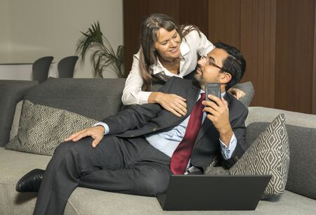 arab man working at home while woman is looking over his shoulder trying to get his attention