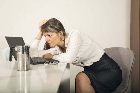 middle aged woman in formalware working in a laptop in her city apartment