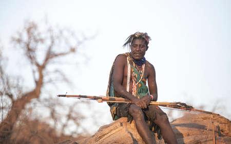 Lake Ayasi, Tanzania, 11th September 2019: hadzabe hunter resting on rocks near his home in nature