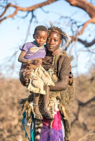 Lake Ayasi, Tanzania, 11th September 2019: hadzabe man carrying his little sister