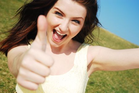 Beautiful young woman giving a thumbs up and smiling in a field with a blue sky