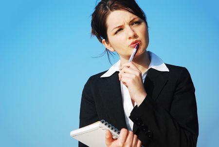 reportero: Una joven y bella mujer de negocios con un bloc de notas haciendo frente a un cielo azul, el pensamiento  contemplando Foto de archivo