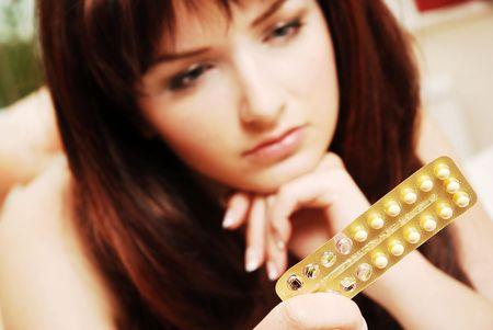 Una bella giovane donna vedendo il suo pillole contraccettive. Profondit� di campo, l'attenzione � sul pillole.