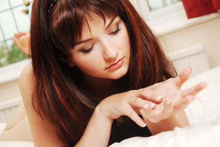 A beautiful young woman in bed looking at her hands. photo