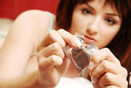 Una donna giovane e bella apertura di un preservativo sul suo letto. Focus sul preservativo in primo piano.
