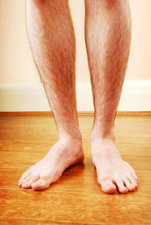 floor standing: A mans legs standing on wooden floor Stock Photo