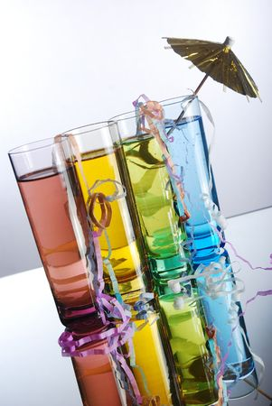 Four multi-colored shot glasses with colored alcohol on a reflective surface with party streamers and umbrella