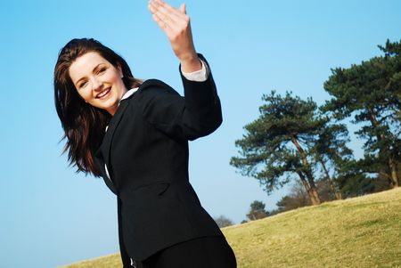 A beautiful young businesswoman leading the way in a field