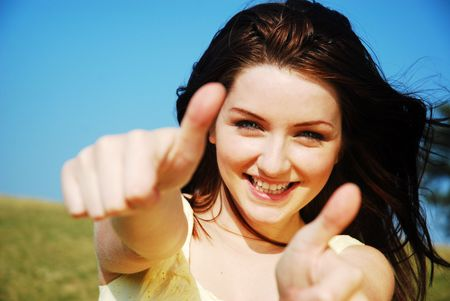 Joven y bella mujer con un pulgar hacia arriba y sonriente en un campo con un cielo azul.