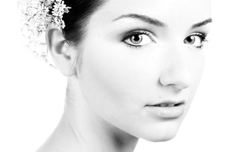 A black and white close-up of a beautiful woman with bridal flowers in her hair. photo