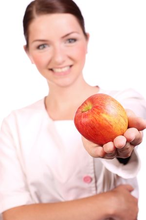 A smiling nursedietician is offering an apple to the camera. Shallow depth of field, focus on the apple. photo