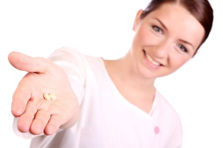 A beautiful young nurse offering two pillstablets to the camera and smiling. The focus is on the pills in the foreground. photo