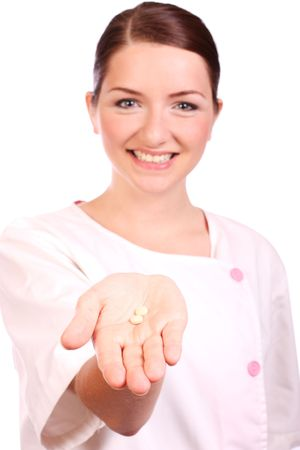 A beautiful young nurse offering pills and smiling to the camera. Focus is on the pills in the foreground. photo