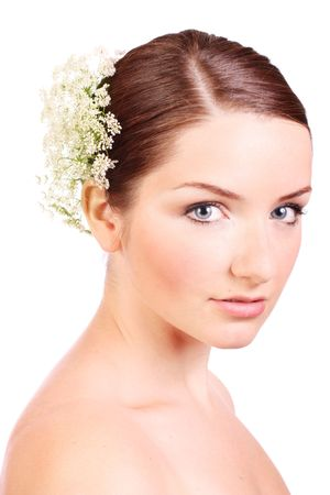 A beautiful young woman with bridal flowers in her hair looking at the camera. photo