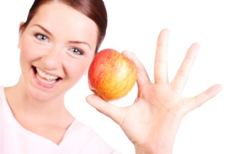 A happy young woman holding up an apple and smiling. photo