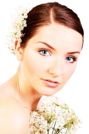 A close up of a beautiful bride with flowers looking into the camera. photo