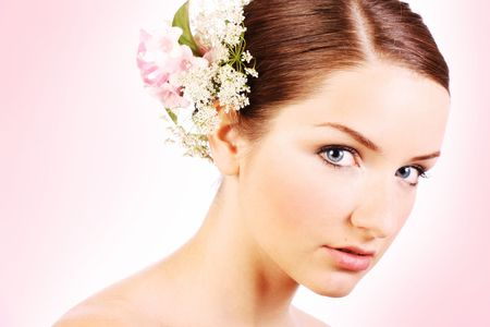 A close up of a beautiful bride looking at the camera in front of a pale pink background.