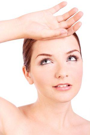 Una bella giovane donna con la sua mano per la testa su uno sfondo bianco.