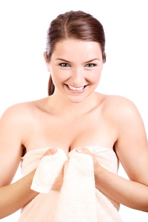 hair wrapped up: A smiling woman holding a bath towel around herself and smiling cheekily to the camera.