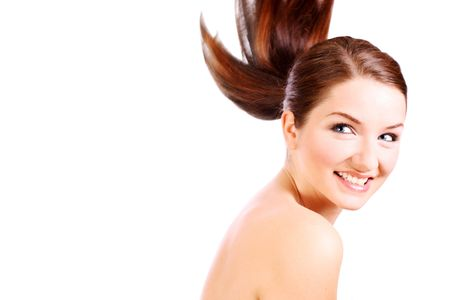 pony tail: A beautiful young woman smiling with her pony tail mid movement, in front of a white background. Stock Photo