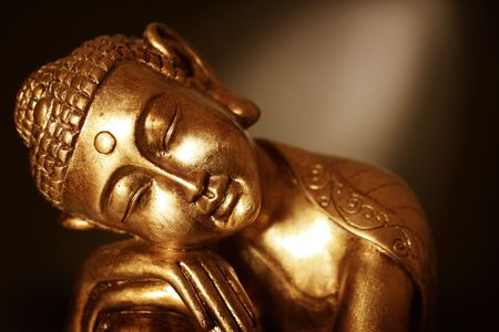 A Buddha statue resting, in front of a dark background with a spotlight. Sepia tones.