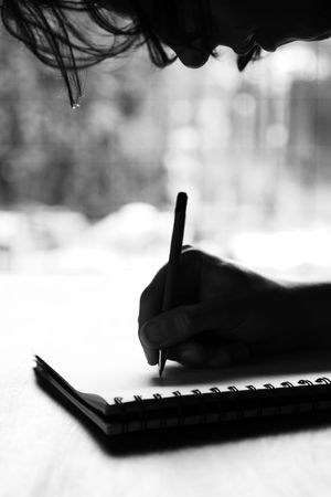 Black and white image of a person writing on a notepad photo
