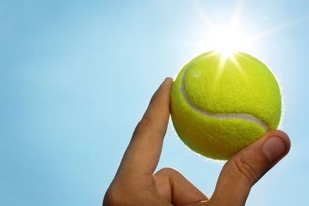 A mans hand holding a tennis ball up to a blue sky with the sun behind it.