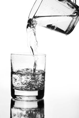 water jug: Water jug pouring into glass Stock Photo