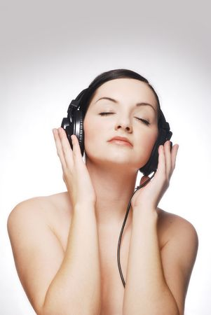 Beautiful brunette woman wearing headphones with closed eyes photo
