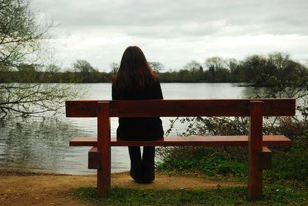 Frau sitzt an einem See Standard-Bild