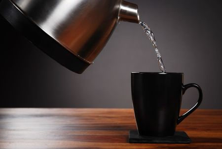 Kettle pouring water into mug on dark background Foto de archivo