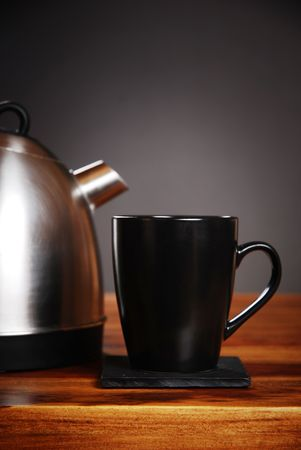 Kettle and mug on dark background photo