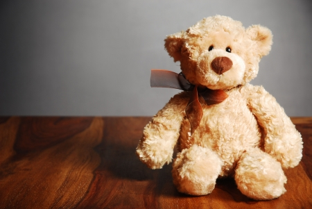 Old fashioned teddy bear on table, dark background Stock Photo