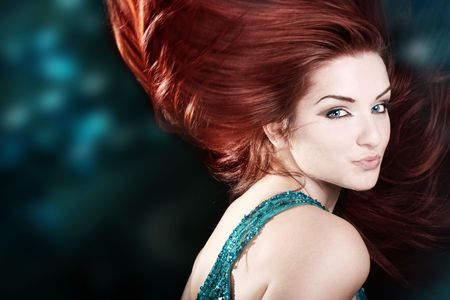 A beautiful fiery redhaired woman with her hair mid movement with a blue abstract background.