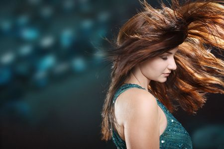 A beautiful fiery redhaired woman with her hair mid movement with a blue abstract background. Disco scene. photo