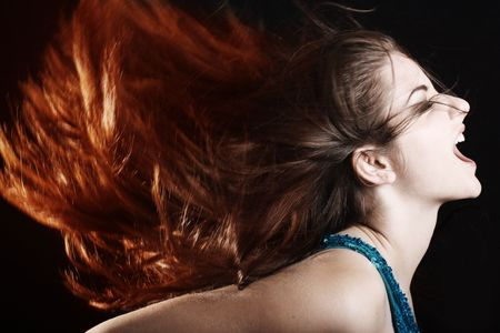 A beautiful young woman wither her fiery hair in motion screaming. photo