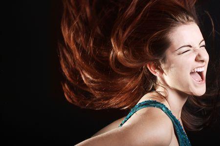 Una donna giovane e bella avvizzire i capelli di fuoco in movimento urlando.