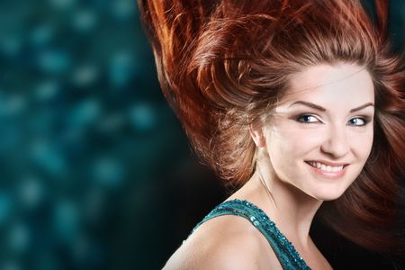 A beautiful redhaired woman smiling with her hair mid movement. Disco scene. photo
