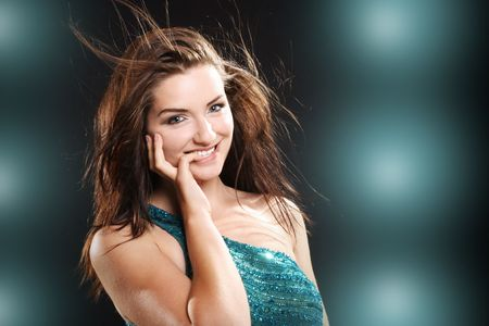 A beautiful young brunette woman with her hair in motion smiling at the camera. photo