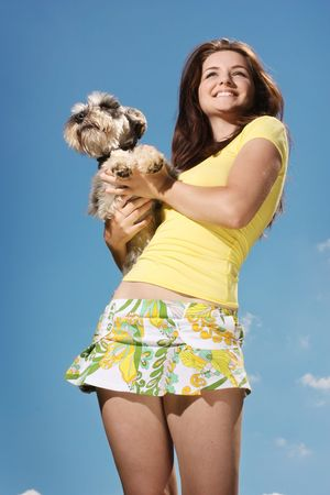 A beautiful smiling girl holding her Miniature Schnauzer on a sunny day in front of a blue sky. photo