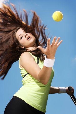Una donna giovane e bella partita a tennis. Azione shot.